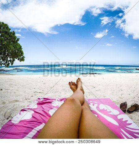 Legs With Fake Spray Tan On Sun Lounger On Tropical Beach With Pink Towel At Lefaga, Upolu Island, W