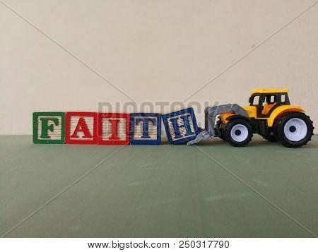 Toy bulldozer with faith wooden block
