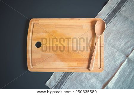 Wooden Cutting Board With Wooden Spoon On Dark Background