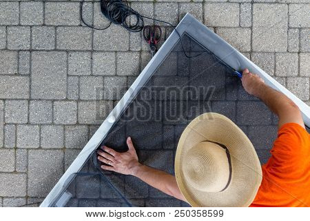 Man Wearing Hat Replacing Old Material In Porch Door