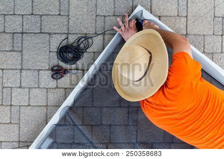 Man Replacing Damaged Wire Mesh On A Screen Door Lying On The Paving On An Exterior Patio Viewed Fro