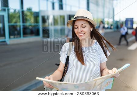 Young Relaxed Traveler Tourist Woman In Hat, Light Clothes Hold Paper Map At International Airport.