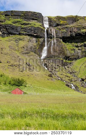 Waterfall And Stream Along The South Coast Of Iceland With A Red Barn