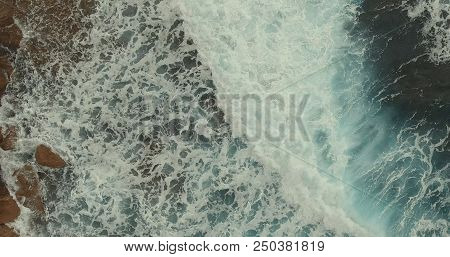 Aerial Photography. High Waves With White Crests Crashed Onto A Rocky Shore