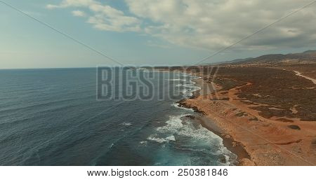 Aerial Photography. The Waves Of The Sea Are Broken Against The Stone Shore. Blue Sky With Fluffy Cl