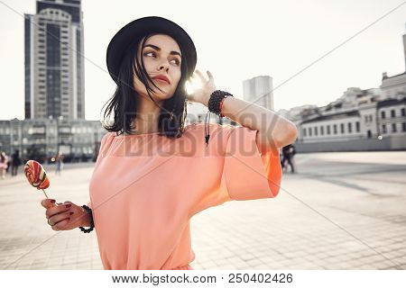 Portrait Of Orderly Pretty Woman Gesticulating Hand While Holding Colourful Sweet Lollipop. She Walk
