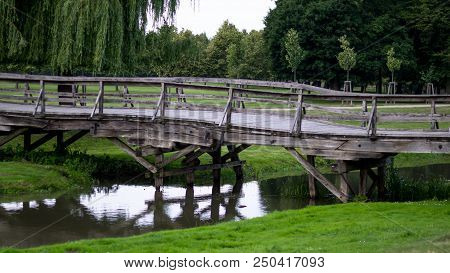 Wooden Bridge Made Of Planks Leading To The Park Above The Stream, The Side View.