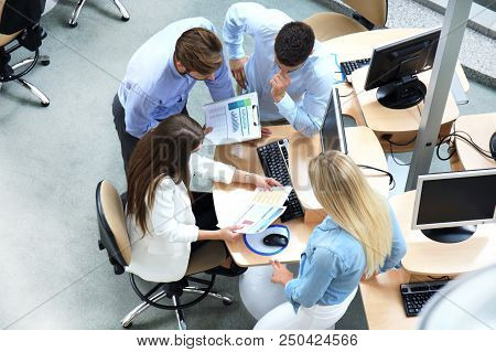 Top View Of Young Modern Colleagues In Smart Casual Wear Working Together While Spending Time In The