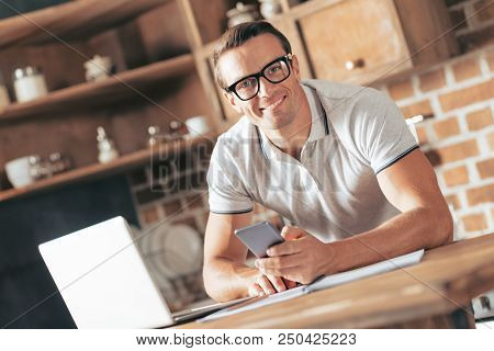 Being Self Employed. Joyful Nice Handsome Man Smiling And Holding His Smartphone While Looking At Yo