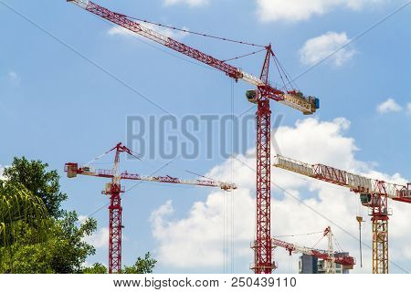 Construction cranes, Tower Cranes against the blue sky with clouds poster