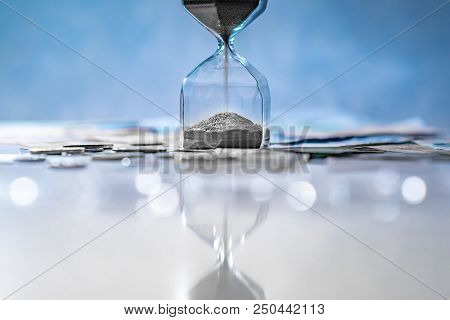 Reflection of sliver sand running through the shape of modern hourglass on glowing table with currency. Time investment and passing time. Urgency countdown timer for business deadline concept poster