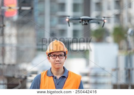 Young Asian engineer man flying drone over construction site. Using unmanned aerial vehicle (UAV) for land and building site survey in civil engineering project. poster