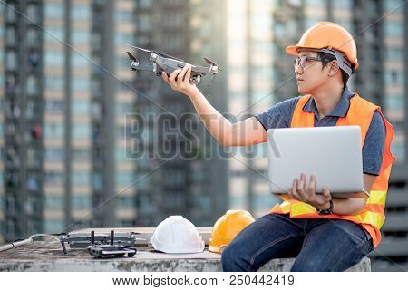 Young Asian man working with drone laptop and smartphone at construction site. Using unmanned aerial vehicle (UAV) for land and building site survey in civil engineering project. poster