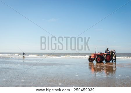Egmond-aan-zee, Netherlands - 2016-04-10: Red Tractor On The Shore And A Fisherman In The Distance D