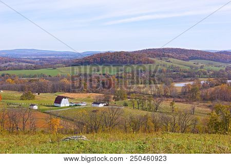 Countryside Landscape In Autumn. A Scenic Farm With Fields And Forests Under The Blue Sky.