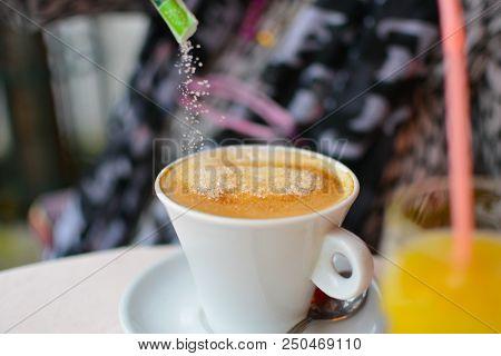 Pouring Granulated Sugar Into A Delicious Cafe Au Lait, Cafe Creme Or Espresso At A Parisian Cafe