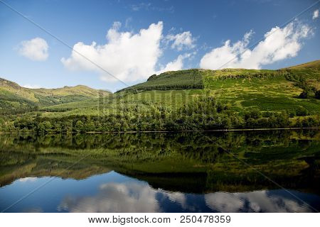 Wooded Hillside Reflected In A Scottish Highland Loch