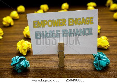 Writing note showing Empower Engage Enable Enhance. Business photo showcasing Empowerment Leadership Motivation Engagement Written notepad stand with paperclip yellow blue lobs on wooden deck poster