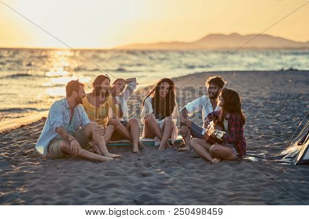 Group of smiling friends with guitar at beach. friends relaxing on sand at beach with guitar and singing
