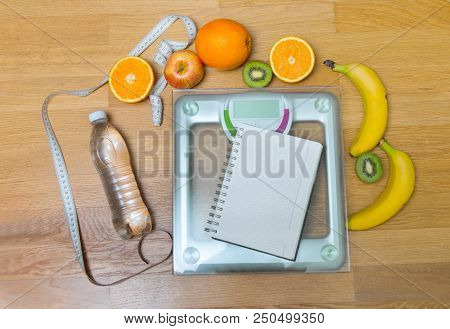 Fruits, Bottle Of Water, Notepad, White Measuring Tape And Weight Scale. Dieting Concept.