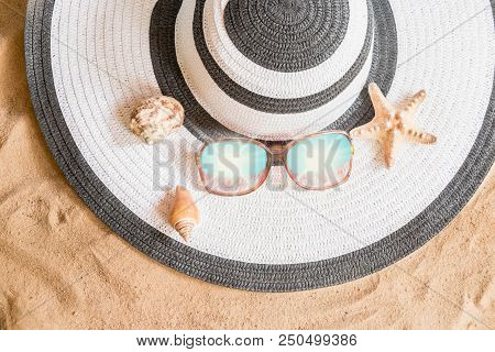 Large Summer Hat, Sunglasses And Seashells On Sand Beach