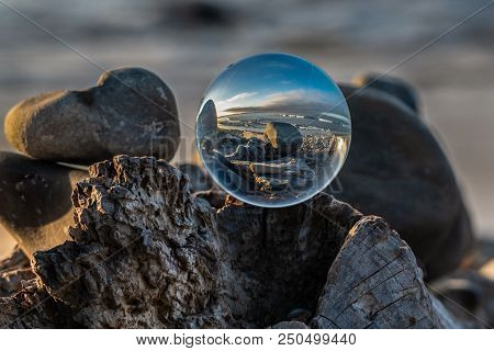 Spherical Lens Sitting Atop Driftwood Log Under The Morning Light Of Dawn Along This California Beac