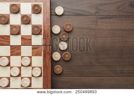 Top View Of Wooden Draughts. Draughts Game On Brown Table. Draughts Board On Wooden Background. Drau