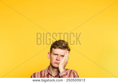 Bored Disinterested Weariful Indifferent Unenthusiastic Man. Portrait Of A Young Guy On Yellow Backg