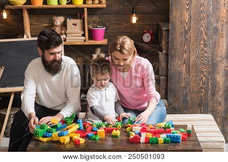 Game Concept. Son With Mother And Father Play Construction Game. Little Child Learning Through Game.