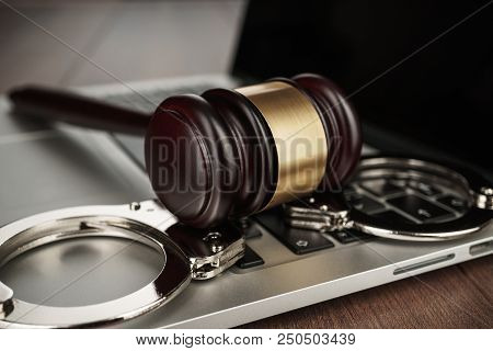 Handcuffs And Judge Gavel Cyber Crime Concept. Cyber Crime Concept Depicted On The Table. Cyber Crim