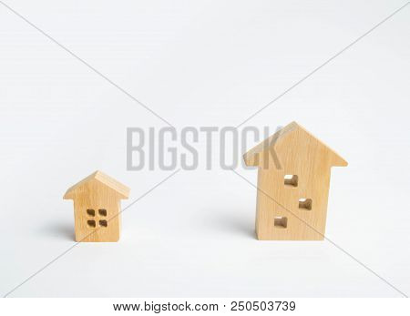 Two Wooden Houses On A White Background. A Large House Better Then A Small One. The Concept Of Buyin