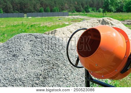 Photo concrete mixer installed on the construction site next to a pile of sand and gravel. poster