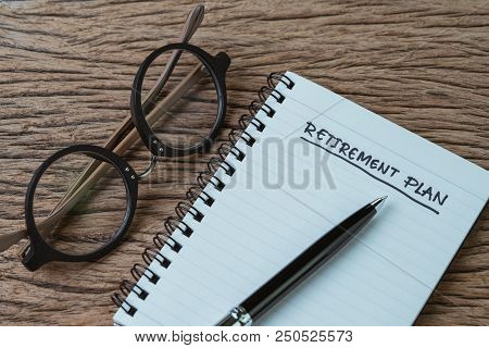 Blank Note Pad With Pen And Handwriting Headline As Retirement Plan With Eyeglasses On Wood Table, P