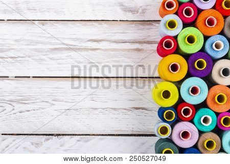 Beautiful Sewing Spools With Bright Vivid Threads Placed On White Rough Wooden Plank Table From Abov
