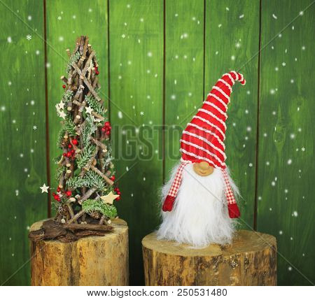 Gnome Standing On A Stump With A Twisted Hat And A Long White Beard Near The Christmas Tree. Gnome S
