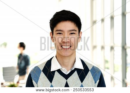 Portrait Of Young Attractive Asian Creative Man Smiling And Looking At Camera In Modern Office Feeli