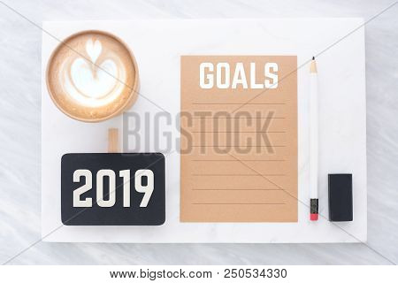 2019 Goals On Brown Recycle Paper With Pencil,clip Blackboard,pencil,eraser And Coffee Cup On White