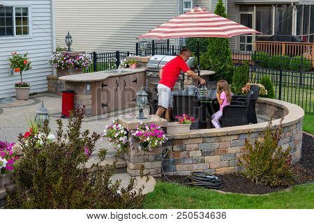 Daddy Serving Lemonade To His Little Daughter Outdoors On A Brick Patio As She Relaxes In The Shade