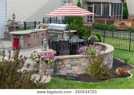 Outdoor Living Space In A Neat Landscaped Garden With Comfortable Wicker Chairs On An Exterior Brick
