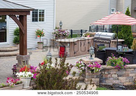Summer Flowers Around An Upscale Brick Patio With Wooden Gazebo, Outdoor Kitchen With Bbq And Comfor