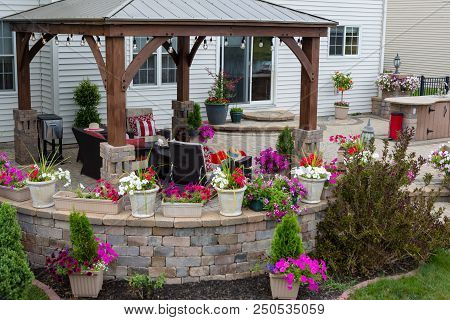 Wooden Gazebo With Aluminum Roof Over A Neat Curved Outdoor Brick Patio Wicker Furniture And Colorfu