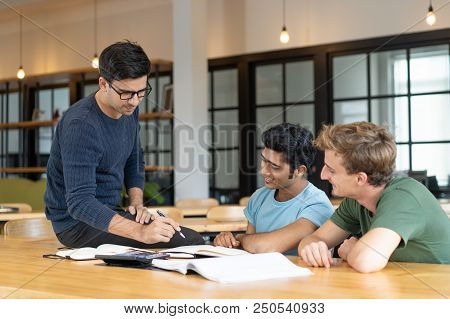 Serious Teacher Checking Assignment Of Two Students. Serious Man In Glasses Pointing Pen At Notes Of