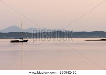 Sailboat On Lake Champlain With A Great View Of The Landscape At Sunset