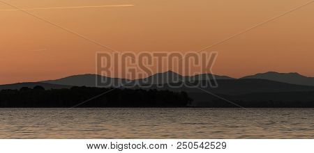 Lake Champlain Sunet And Mountains In Vermont