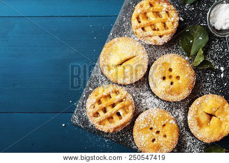 Delicious Mini Apple Pies On Blue Background From Above. Autumn Pastry Desserts.