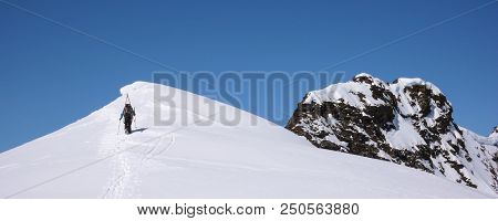 Male Back Country Skier Hiking Along A Narrow Snow Ridge With A Great Mountain Landscape Behind Him