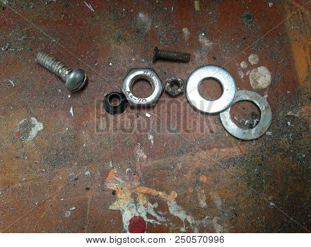 Screw, Bolt, Washers, Nuts On An Old Grungy Dirty Workbench In An Engineering Workshop
