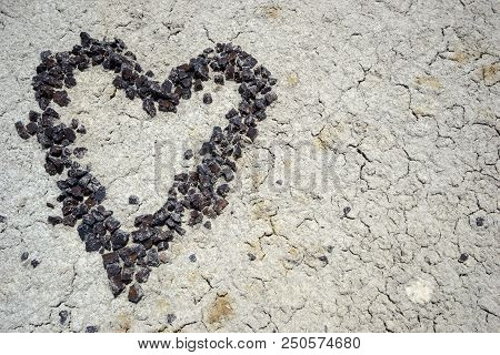 Sonne Heart Made Of Red Pebbles On A Cracked Desert Dirt Background