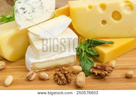 Pieces Of Different Hard, Medium-hard, Soft And Semi-soft Cheese With Mold, Various Nuts And Greens