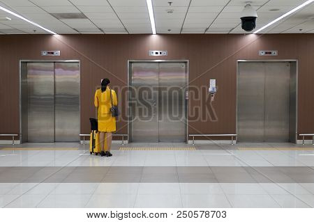 Air Hostess With Yellow Uniform Is Checking Her Flight Schedule And Waiting Elevator At The Internat